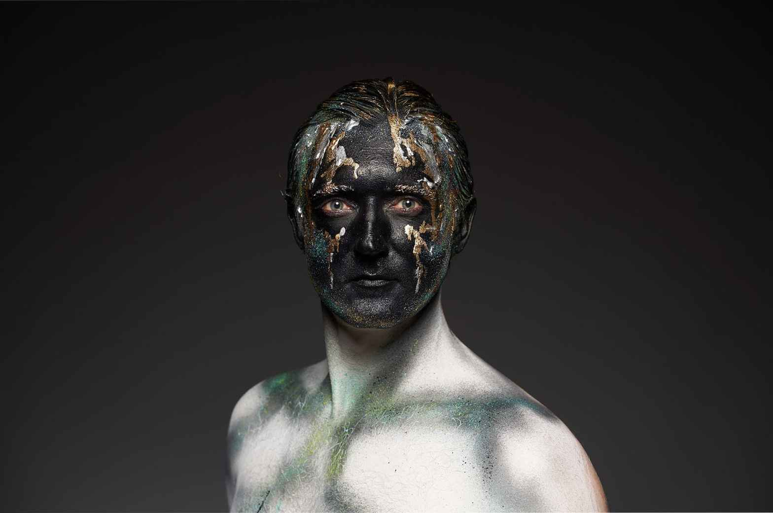 man with black and gold body art